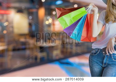 Asian Woman Shopping Holding Shopping Bag And Use Of Mobile Phone At Shopping Center. Consumerism, S