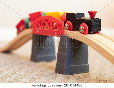 Wooden Toy Train Running On Miniature Bridge. The Black Engine Pulling Colorful Cars On The Floor. E