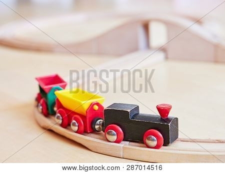 Wooden Toy Train Running On Miniature Railway Tracks. The Black Engine Pulling Colorful Cars On The