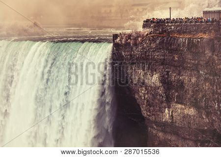 View Of Niagara Falls From Canada, Day Time. Some People Overlook A Balcony Right Next To The Waterf