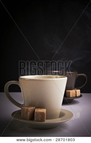 two cups of hot beverage on mixed white and black background