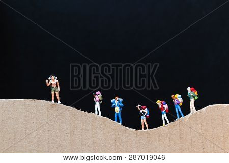 Miniature People :  Traveler With Backpack Walking On The Paper Mountain  . Travel And Trekking Conc