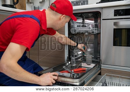 Home Appliance Maintenance - Repairman Repairing Dishwasher In Kitchen