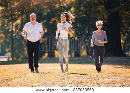 Senior Man And Woman And Young Female Instructor  Workout On Fresh Air. Outdoor Activities, Healthy