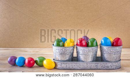 Drei silberne Becher mit viele bunte Ostereier Vor einem Holz Hintergrund poster