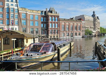 Amsterdam, Netherlands. Beautiful Old Buildings On The Bank Of The Amstel River In The Old Town