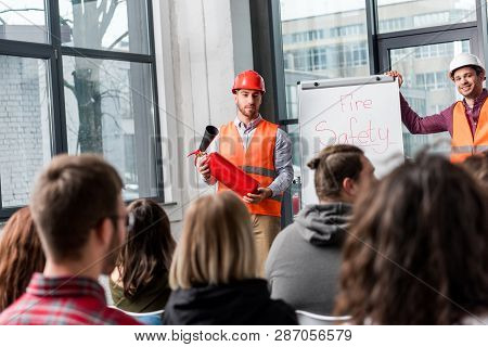 Selective Focus Of Handsome Fireman In Helmet Holding Extinguisher While Standing Near White Board W