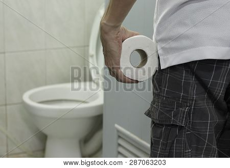 Hand Holding Toilet Paper Roll And Entering The Toilet