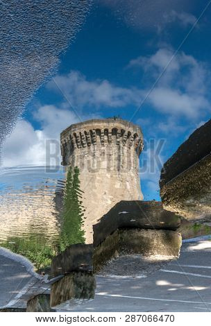 Upside down picture with a castle tower reflection on water in Avignon