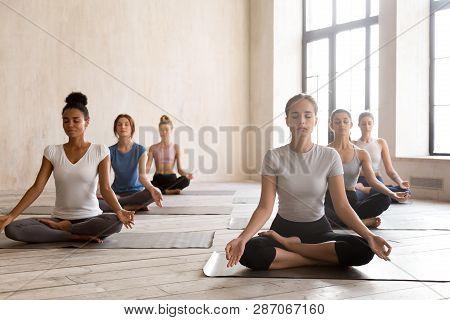 Group Of Young Women Practicing Yoga, Ardha Padmasana Exercise