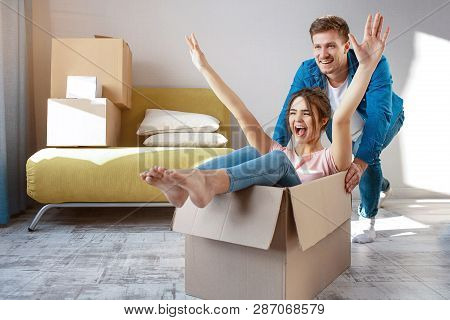Young Family Couple Bought Or Rented Their First Small Apartment. Cheerful Happy People Having Fun.