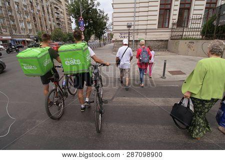 Bucharest, Romania - August 15, 2018: Two Uber Eats Couriers Cross The Street Near Coltea Hospital I