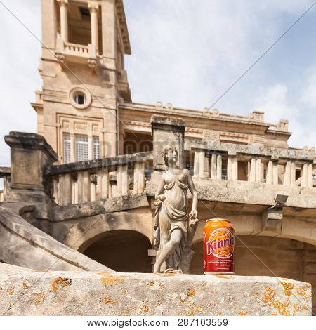 Paceville, Malta - Jun 18 2010: Focus On A Can Of Kinnie With A Historic Mansion And An Ancient Scul