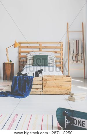 Real Photo Of A Bedroom Interior With A Bed And Pallet As A Headrest