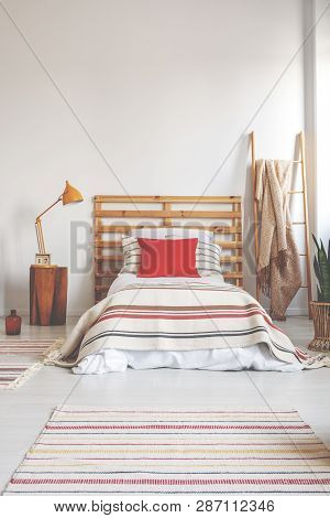 Red Pillow On Single Bed With Striped Bedding In Spacious Bedroom Interior, Real Photo With Copy Spa