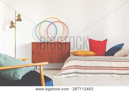 Hula Hoops On A Cupboard Next To A Bed With Colorful Pillows In A Retro Bedroom Interior