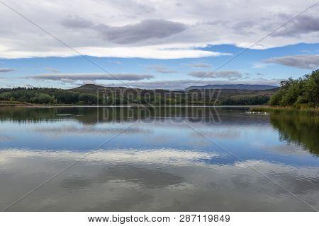 Overcast Sky Reflections On Pantano De La Grajera Or La Grajera Reservoir Surface On The Way Of St.