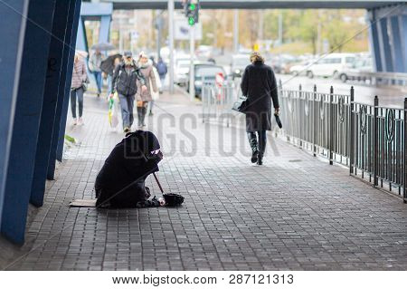 Kiev, Ukraine - October 24, 2018: Beggarly Old Woman Sits On The Sidewalk Surrounded By Passersby