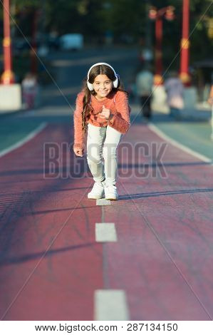 Ready To Run. Little Girl Standing On Start Line While Running Outdoor. Little Girl Listen Music. Mp