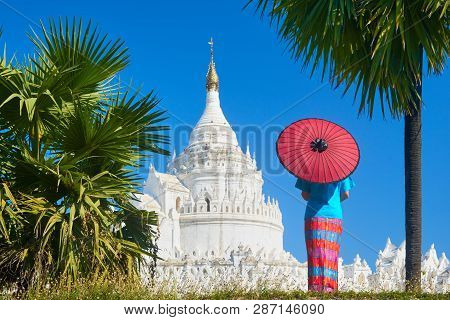 A Young Woman In Traditional Dress With An Umbrella Is Looking At The Hsinbyume-paya Pagoda Near The