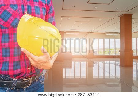 Engineer Check In Decorate Interior Room And Hand Holding Yellow Helmet. Concept Construction Backgr