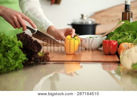 Unknown Human Hands Cooking In Kitchen. Woman Slicing Yellow Bell Pepper. Healthy Meal, And Vegetari