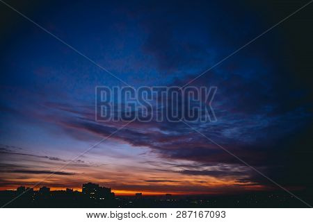 Cityscape With Vivid Warm Dawn. Amazing Dramatic Blue Violet Cloudy Sky Above Dark Silhouettes Of Ci