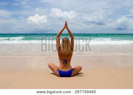Young Woman Makes Meditation In Lotus Pose Oon Tropical Beach With Waves Harmony And Contemplation.