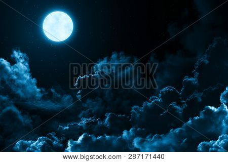 Bright Full Moon In The Mystical Midnight Sky With Stars Surrounded By Dramatic Clouds. Dark Natural