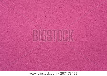Pink painted stucco wall on Burano Island in the Venetian Lagoon near Venice, Italy. Background texture.