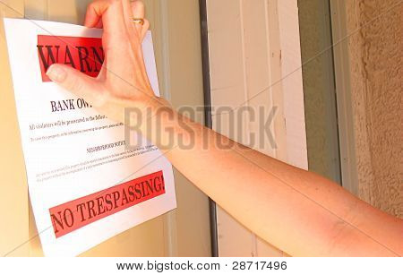 Hand Taking Down No Trespassing Sign