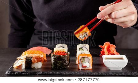 The Concept Of Japanese Cuisine. A Girl Holds A Red Chinese Chopsticks And Eat Sushi In A Restaurant