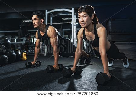 Young Couple Is Working Out At Gym. Attractive Woman And Handsome Muscular Man Are Training In Light