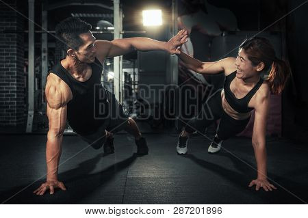Young Sporty Couple Working Out Together At Gym, Fitness Man And Woman Giving Each Other A High Five