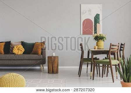Vintage Living And Dining Room Interior With Retro Table With Chairs And Comfortable Sofa With Pillo