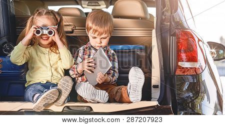 Little Cute Kids Having Fun In The Trunk Of A Black Car With Suitcases. Family Road Trip