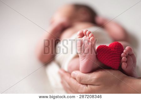 Mothercare Newborn Concept. Mother Holding Baby Feet And Heart