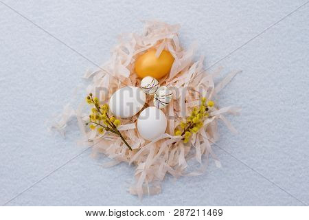 Delicate Easter composition in nest. White eggs, artificial eggs and golden egg decorated with pussy-willow twigs in paper nest, top view. poster