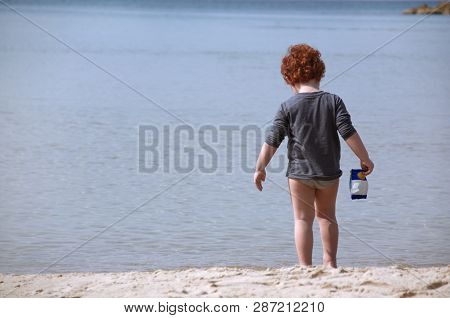 Red-haired Child On The Background Of The Sea