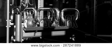Black Kettlebells With 4kg Of Weight On Metal Rack In Sports Gym. Sunlight Falls On Metal Rack With
