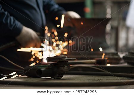 Close-up Of Angle Grinder On Background Of Blacksmith Doing Welding Repair Work Using Professional E
