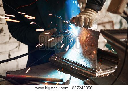 Close-up Of Blacksmith Hands Doing Welding Repair Work Using Professional Equipment In Workshop. Man