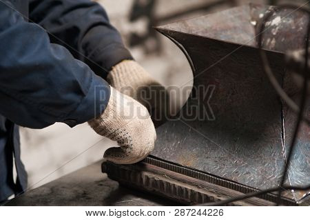 Close Up Of Hands Of Blacksmith With A Metal Plate In Workshop. The Blacksmith In White Gloves Is Wo