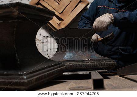 Blacksmith In Workshop Soldering Metal Object With Ornament. The Blacksmith In White Blacksmith Glov