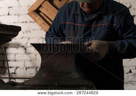 Blacksmith In Workshop Soldering Metal Object. The Blacksmith In Work Clothes In White Blacksmith Gl