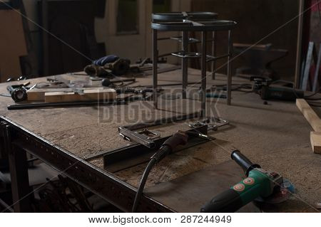 Blacksmith Workshop Table With Metal Grinder Equipment And Nozzles With Manifactured Metal Chairs. M