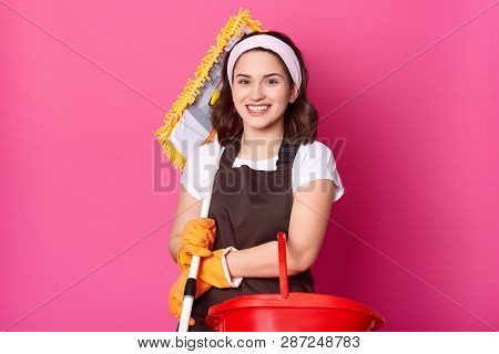 Cheerful Brunette Woman Holds Mop And Bucket. Girl Woks As Maid. Smiling Housewife. Woman Cleans Hom