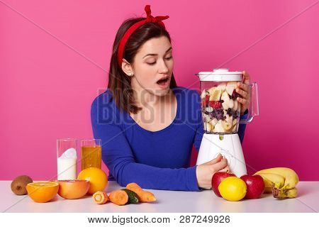 Surprised Dark Haired Female With Red Headband, Turns On Button On Food Processor Filled With Pieces