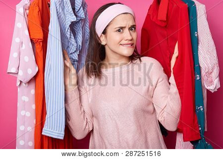 Beautiful Young Girl In Pink Shirt Has Shopping In Fashion Boutique. Pretty Lady Chooses Dress In Cl
