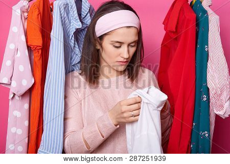 Young Woman Holds New Shirt, Chooses Clothes On Rack In Showroom. Lady Has Hole On Shirt. Upset Fema